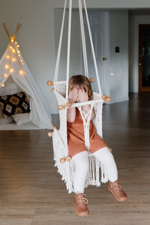 Little kid covering face with hands while chilling in hanging chair