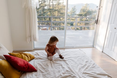 From above of adorable little child in casual clothes playing on bed against wide window while spending time at home