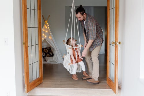 Full body of adorable girl in woven hanging swing seat near helping father in studio