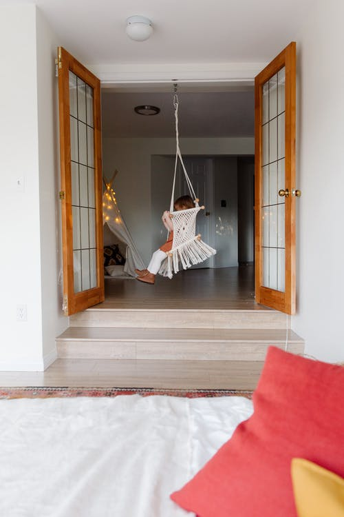 Interior of modern hallway with child in swing chair in cozy house