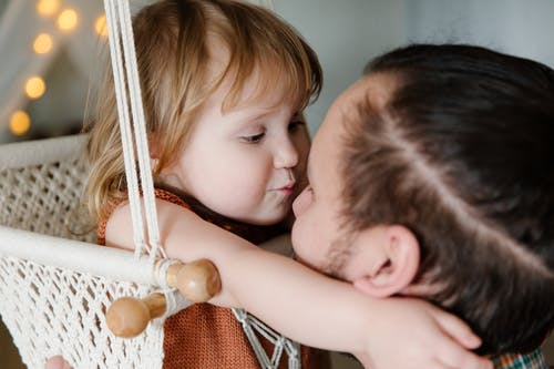 From above of funny little girl embracing male parent and trying to kiss nose of father while chilling together in room
