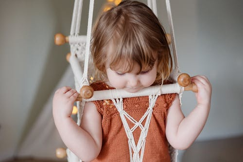 Adorable little girl playing in nursery room while sitting in woven swing