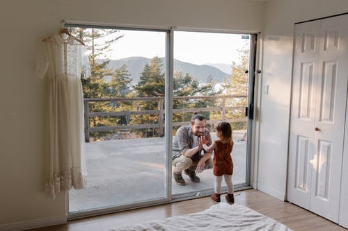 Dad and daughter touching with palms to each other through glass