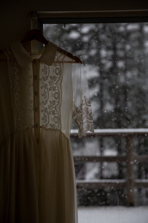 Old fashioned light white dress with lace and buttons hanging on hanger by window in rainy day