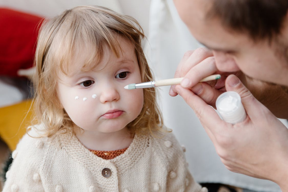 Crop brown haired man with paintbrush drawing white points on face of blond little girl