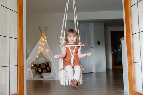 Adorable girl sitting on swing at home