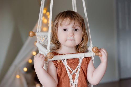 Little girl sitting on woven swing
