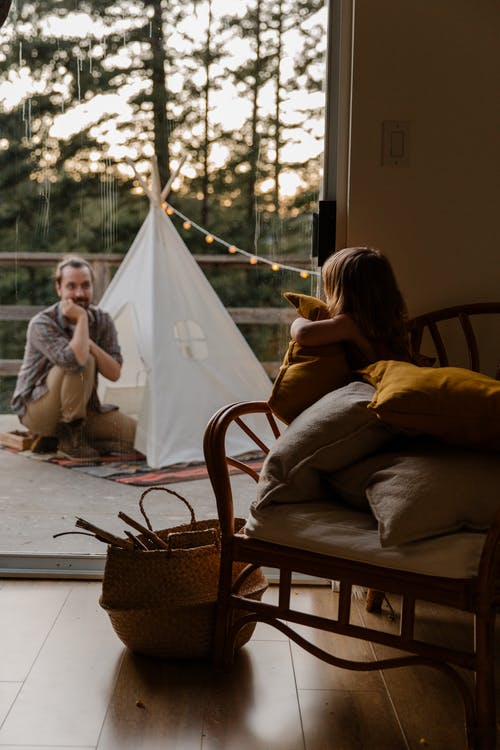 Little child hugging cushion resting in armchair in room and looking at father while dad sitting on floor of terrace near wigwam