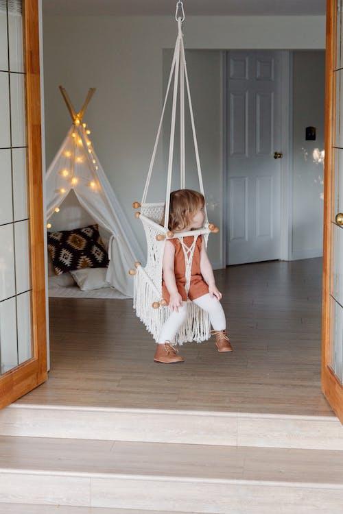 Little girl resting on swing in cozy room
