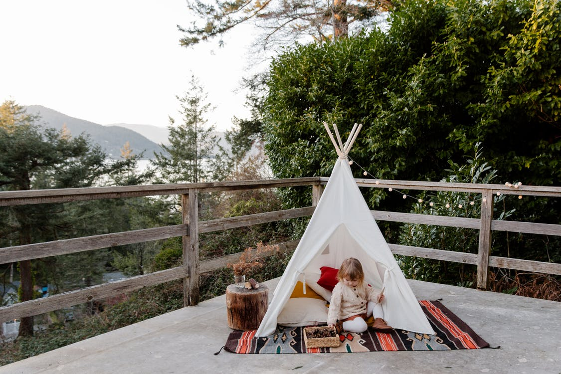 Adorable little kid sitting on rug in wigwam located on terrace with wooden border and scenic view