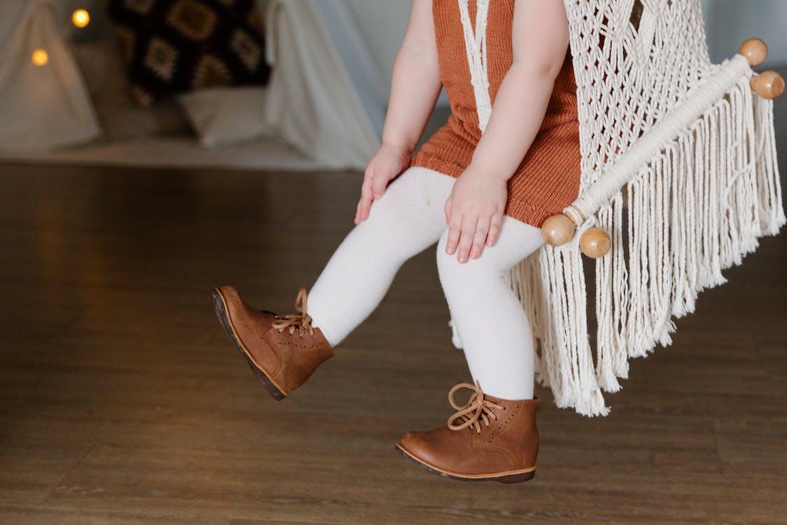 Crop little girl swinging on swing