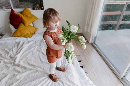 Photo Of Kid Holding Flowers
