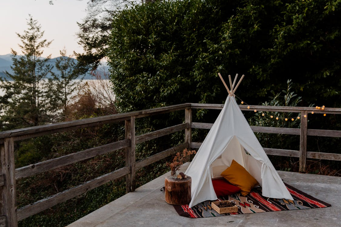 Boho styled tent with rug and pillows located on terrace with wooden fence with picturesque view to sea forest and mountains