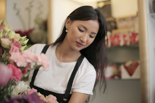 Happy woman in uniform with flowers in shop