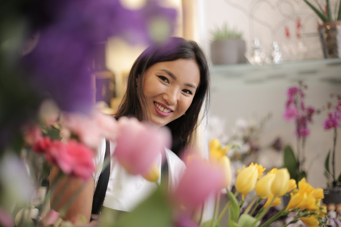Positive Asian black haired lady in uniform standing with colorful flowers in floral shop and smiling