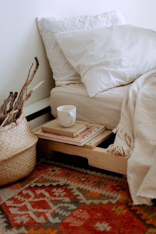 Comfortable cozy bedroom with bed wooden shelves with book and cup while wicker basket with sticks placed on ethnic styled rug