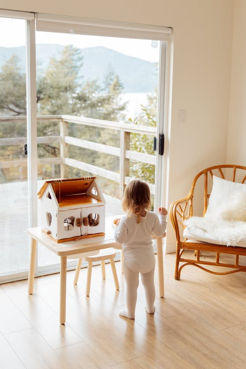 Cute little girl playing with toy house at table near window