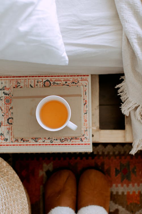 White Ceramic Cup on Brown and White Floral Rug