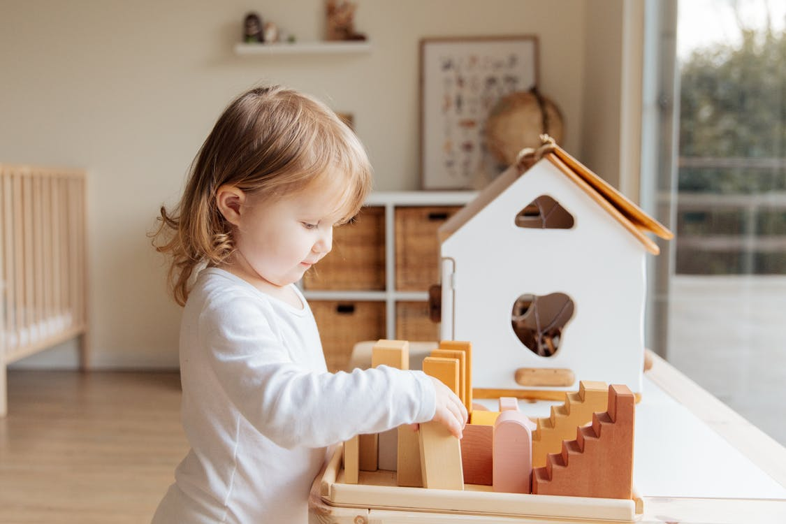Cute little girl playing with wooden blocks at table near window at home