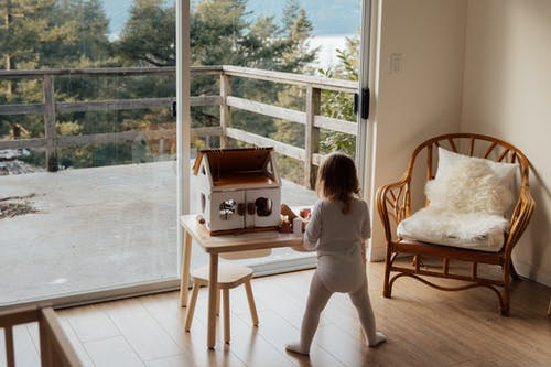 Cute little girl playing with toy house at table near window at home
