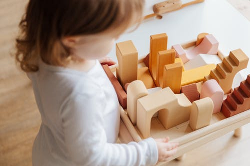 Unrecognizable little girl playing with wooden blocks at table at home
