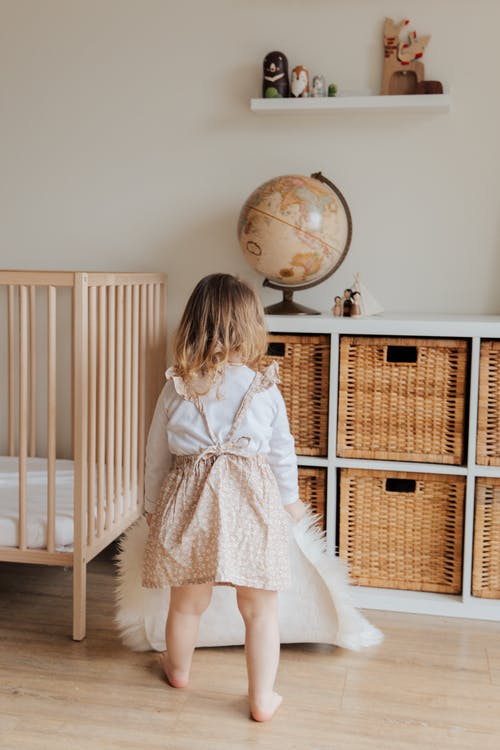 Girl in White Dress Standing Beside Brown Wooden Crib