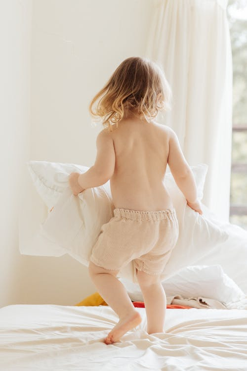 Back view of anonymous little girl in casual clothes playing with pillows on comfortable bed in light room at home