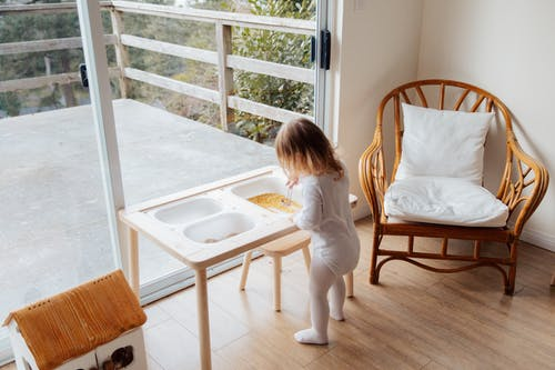 Little girl playing with toys at table near window at home
