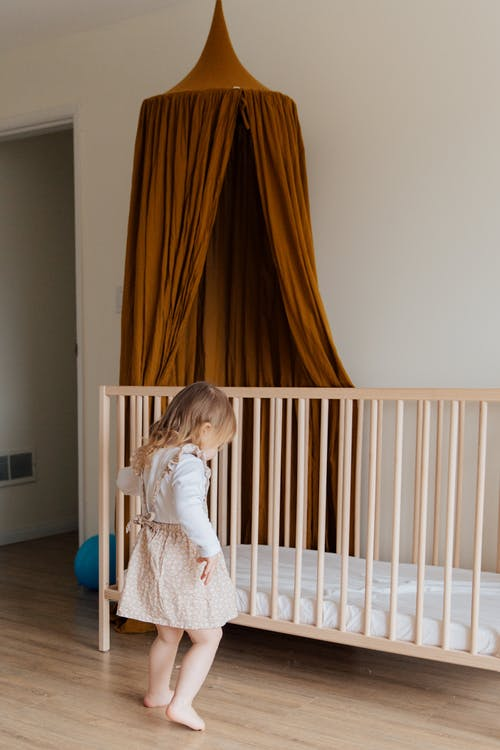 Photo Of Child Standing Near Crib