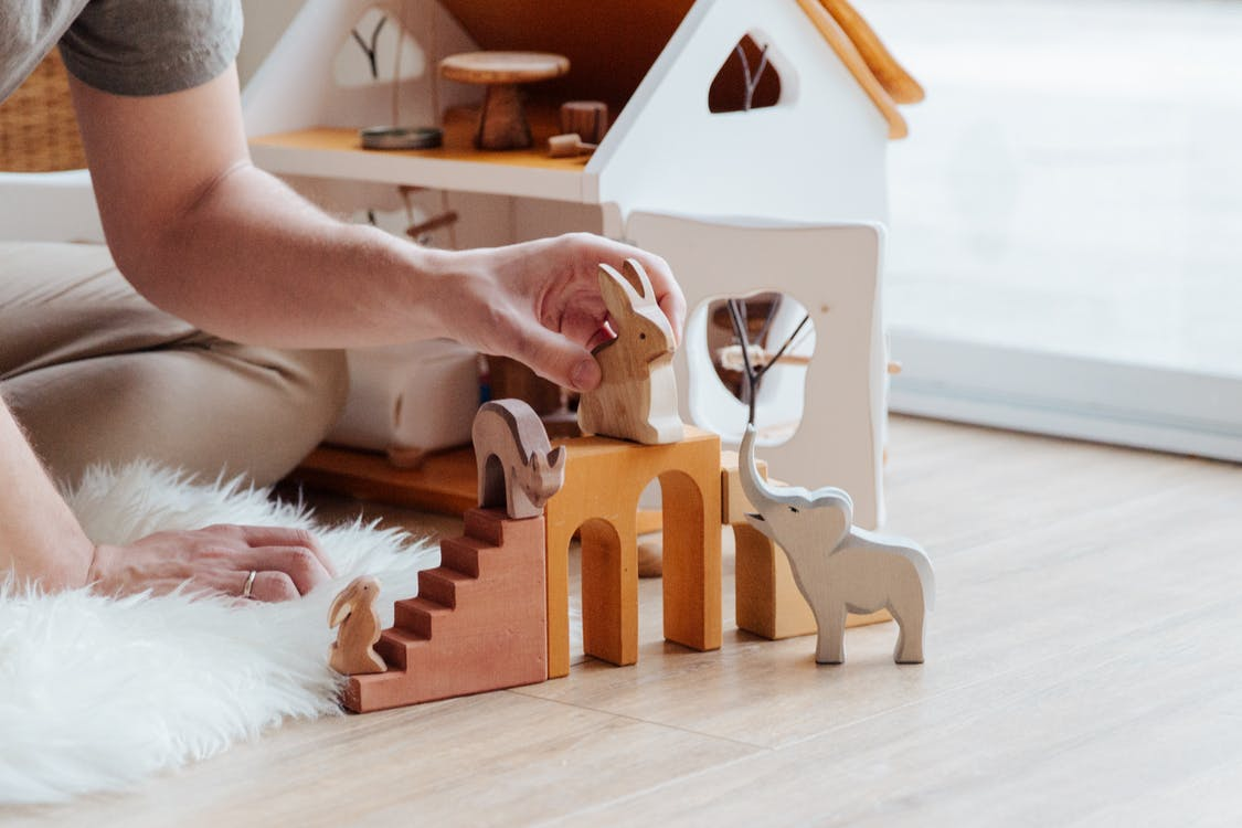 Anonymous crop parent playing with toys on floor at home