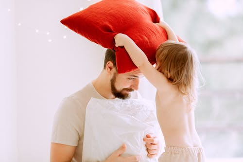 Baby Girl Putting A Red Pillow On Her Father's Head