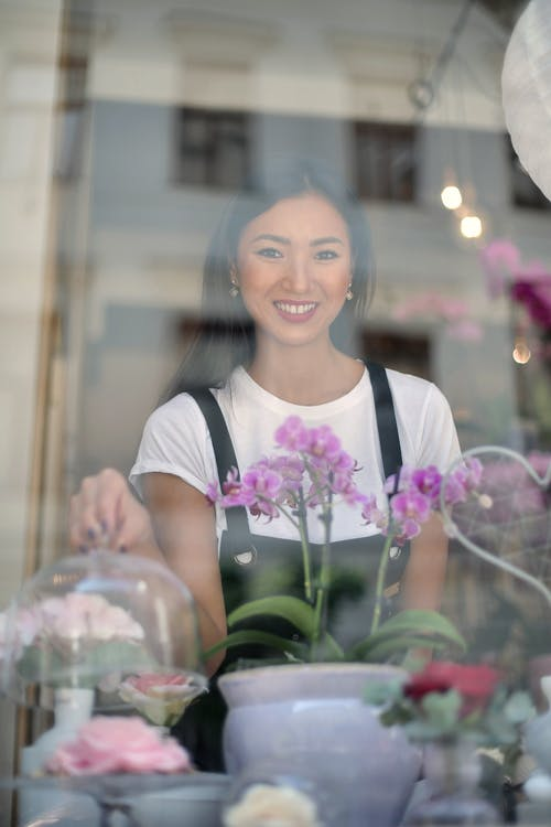 Smiling young Asian waitress female in apron looking at camera while standing behind glass window with beautiful flowers on windowsill in coffee shop and holding clear glass lid over dessert on cake stand