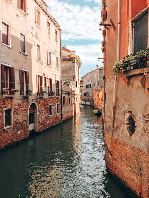 Calm surface of narrow channel among old houses with brick walls located in old town