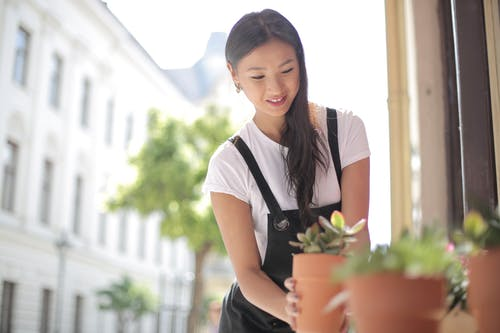Woman in White T-shirt Holding Green Plant