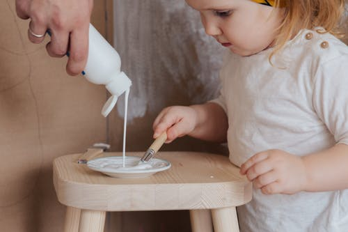 Anonymous cute toddler girl holding brush for getting white paint from plate standing on chair
