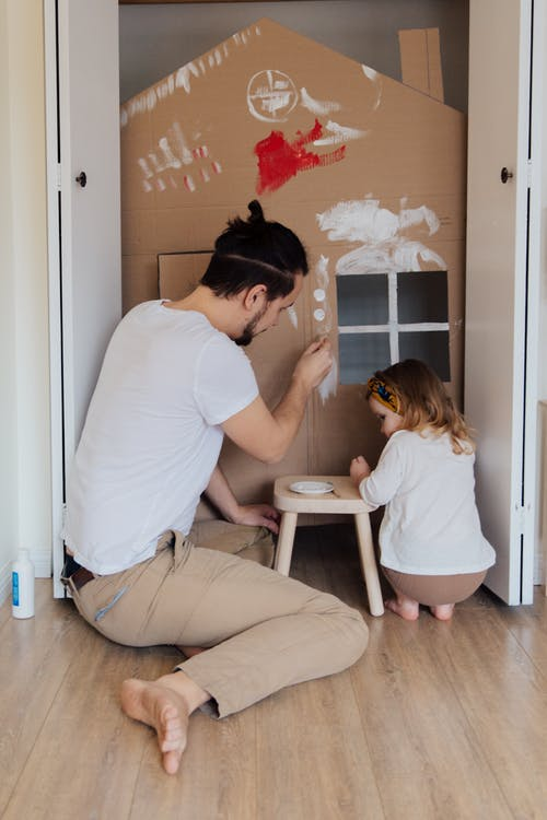 Man in White T-shirt and Brown Pants Painting Cardboard House