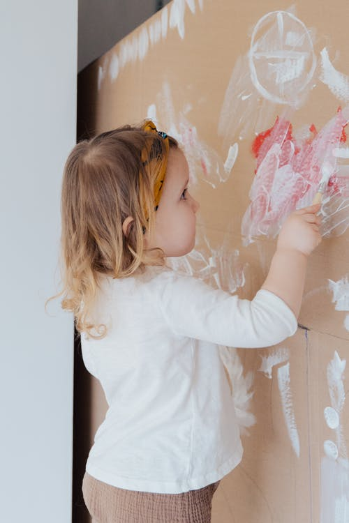 Girl in White Long Sleeve Shirt Holding Paint Brush