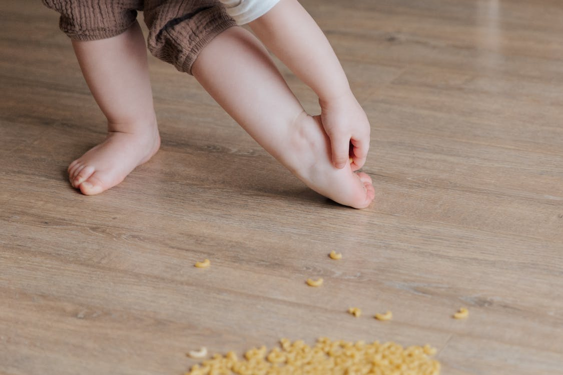 Crop faceless toddler standing barefoot on floor and trying to remove stuck pasta from foot while playing and developing fine motor skills at home