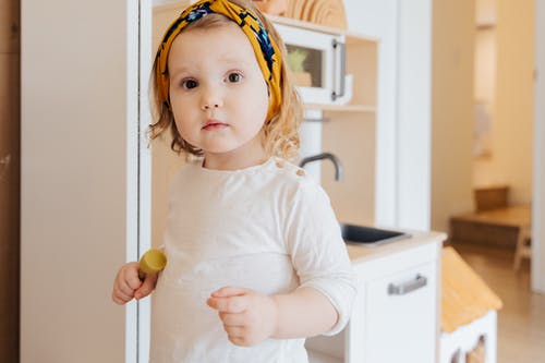 Girl in White Long Sleeve Shirt Holding Yellow Plastic Toy