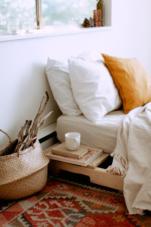 Stylish cozy bedroom interior with bed located near window with white linen, cushions,  tray with cup of coffee, basket with dry wooden branches and carpet on floor