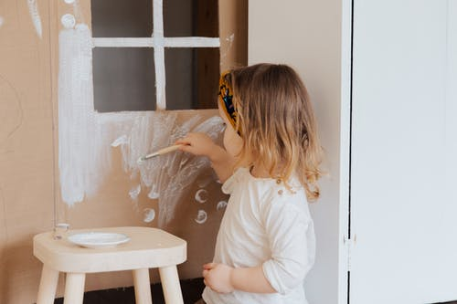 Girl in White Shirt Painting on Cardboard Play House