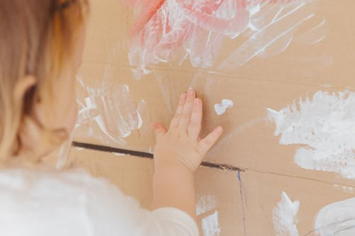 Crop anonymous child drawing with white paint at home