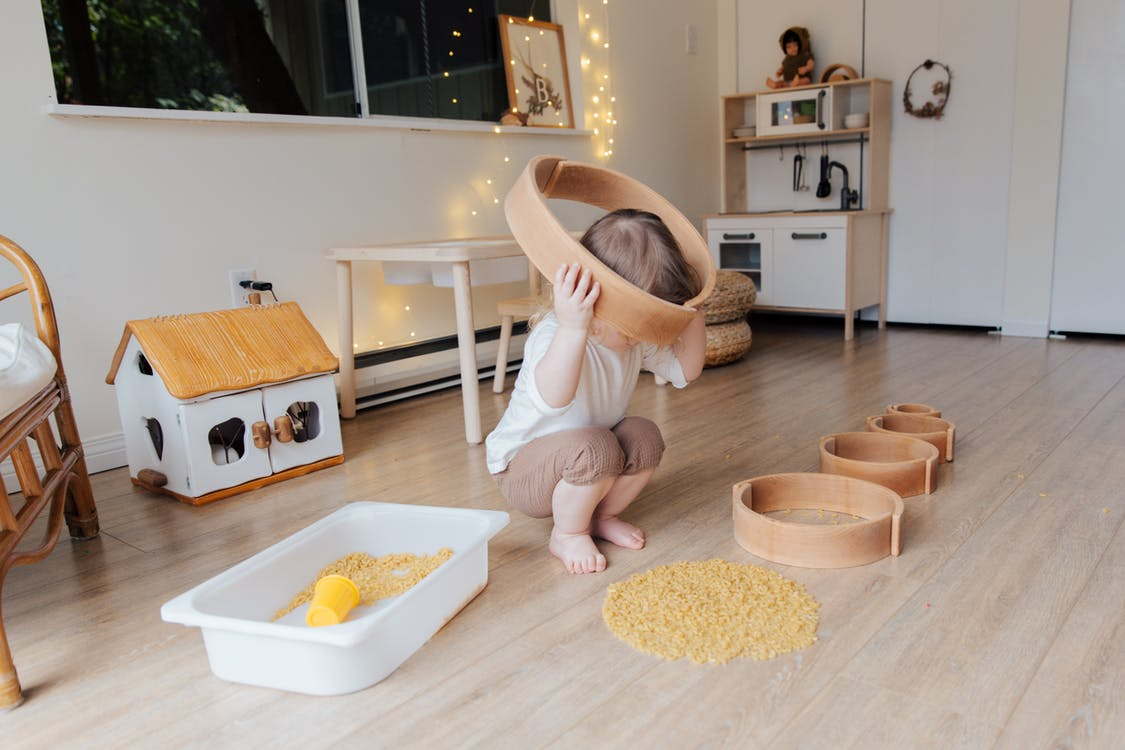 Full length of anonymous toddler squatting barefoot on floor playing with round wooden shapes of different size and pasta and putting biggest shape on while developing fine motor skills at home
