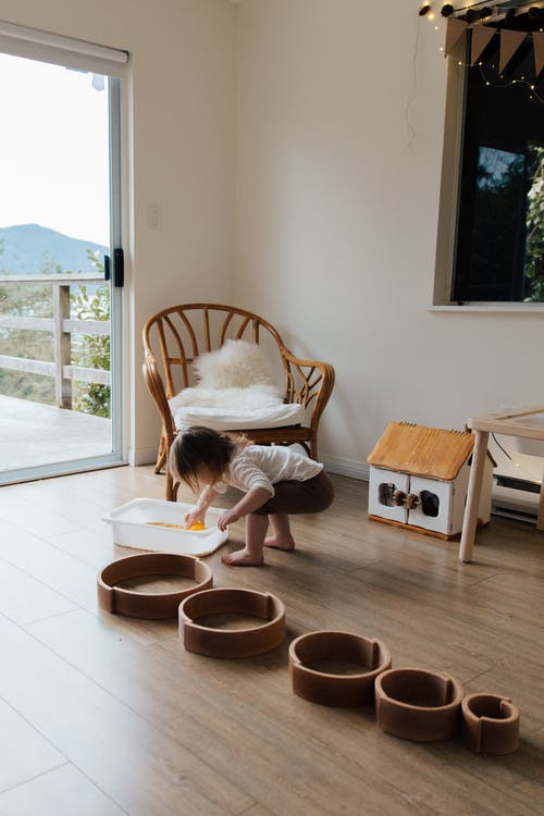 Full length back view of faceless toddler standing barefoot on floor playing with round wooden shapes of different size and using white container while developing fine motor skills at home