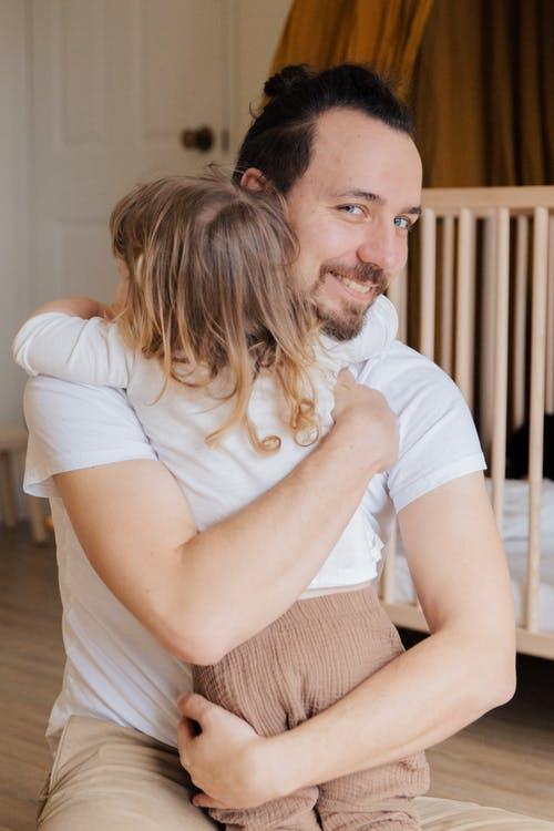 Man in White T-shirt Hugging Child in White T-shirt