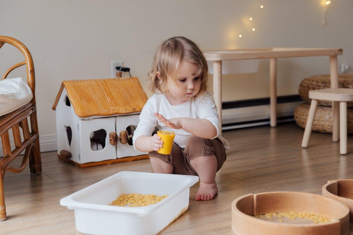 Girl Holding Yellow Plastic Cup Full of Macaroni