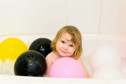 Photo Of Child Surrounded By Balloons