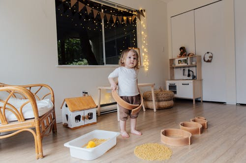 Toddler girl playing with wooden shapes of different size and pasta while trying to put biggest shape on
