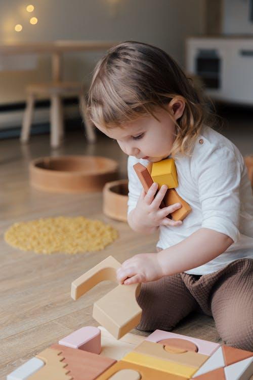 Photo Of Child Holding Wooden Blocks