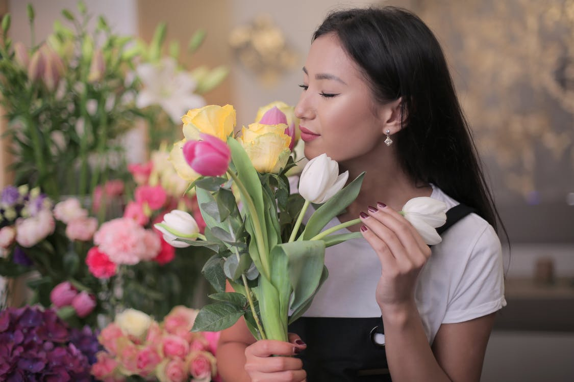Woman in White Shirt Holding Yellow, White and Pink Tulips